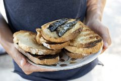Man with a plate of bread and sardines. Closeup of a young caucasian man with a plate with some slices of toasted bread and some roasted sardines stock photos