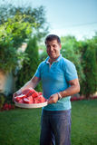 Man with a plate of sliced watermelon Stock Image