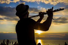 Man play the flute at sunset on the beach during a full moon party in island Koh Phangan, Thailand Royalty Free Stock Photos
