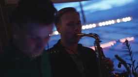 Man play on gold saxophone on party in nightclub. Performance. Dj at turntable. stock footage