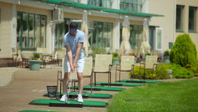Man play golf near the clubhouse stock video footage