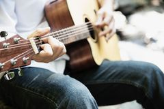 Man play guitar new to the waterfall royalty free stock images