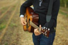 Man play guitar. Man playing romantic music on guitar on field stock photos