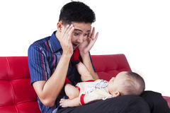 Man play peekaboo with his child. Young father sitting on the sofa while playing peekaboo with his baby boy, isolated on white Royalty Free Stock Images