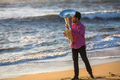 Man play the trumpet on Ocean coast during surf. Concert. Man play the trumpet on Ocean coast during surf Stock Images