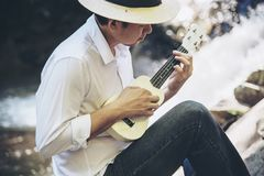 Man play ukulele new to the waterfall royalty free stock photography