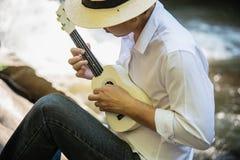 Man play ukulele new to the waterfall stock image