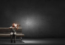 Man play violin. Young handsome man sitting on bench and playing violin Royalty Free Stock Image