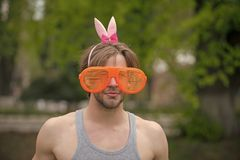 Man, playboy, valentines day, easter., love games. Muscular man in glasses and pink ears on natural background. fashion and party celebration. spring and royalty free stock photo