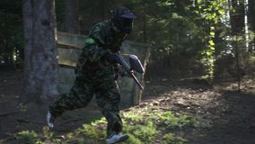 Man player in paintball game with gun running on shooting range in forest. Man player in paintball game with gun running on shooting range slow motion. Paintball stock footage