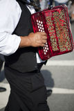 Man playing accordion. A man playing a red accordion Royalty Free Stock Photography