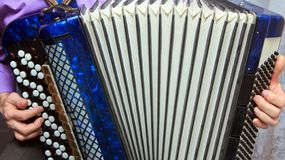 A man playing the accordion. Close up stock image