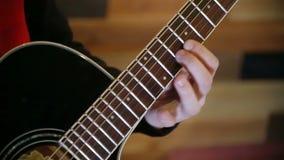 Man playing at acoustic black guitar, close up shot stock footage