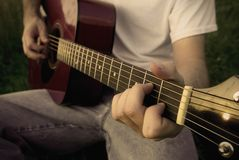 Man playing acoustic guitar. A man playing a red wood acoustic guitar in the grass. Image is done in a dark style with high contrast and a bit of a sepia Royalty Free Stock Image