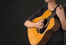 A Man Playing Acoustic Guitar in Black background . Photo for ma. Gazine ,or design work stock photo