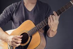 A Man Playing Acoustic Guitar in Black background . Photo for ma. Gazine ,or design work stock images