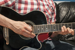 Man playing acoustic guitar. Playing chords on a black acoustic guitar Stock Photo