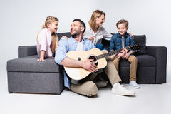 Man playing acoustic guitar with family sitting on sofa near by. Smiling men playing acoustic guitar with family sitting on sofa near by stock photos