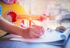 Man playing acoustic guitar. And holding pencil writing note  with sunlight flare Stock Photo