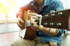 Man playing acoustic guitar with light flare Royalty Free Stock Photography