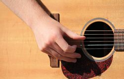 Man playing an acoustic guitar. Man playing live music on an acoustic guitar in the sunshine Stock Images
