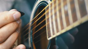 Man playing an acoustic guitar with a mediator. Slow motion