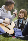 Man playing acoustic guitar outdoors Stock Photography