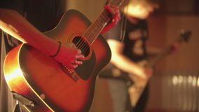 A man playing acoustic guitar - a performance with band in the club. Mid shot stock video footage