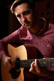 Man Playing Acoustic Guitar In Recording Studio Stock Image