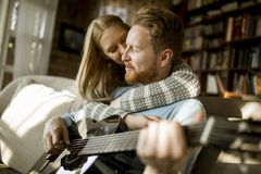 Man playing acoustic guitar on sofa for his young beautiful woman stock photography