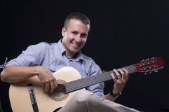 Man playing acoustic guitar Stock Photography