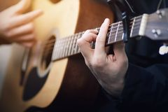 A man playing on an acoustic six-string guitar, holding his hand chords. A man in black clothes playing on a wooden acoustic six-string guitar beautiful melody royalty free stock image