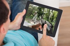 Man Playing Action Game On Digital Tablet Royalty Free Stock Photography
