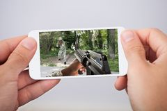 Man playing action game on smartphone Stock Images