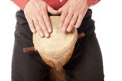 Man playing African drum on his lap. Male figure playing and drumming on African drum on his lap Royalty Free Stock Photography