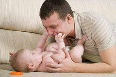 The man is playing with baby. The young man is playing with his little daughter Royalty Free Stock Image