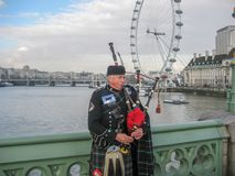 Man playing bagpipe, dressed in traditional scottish costume on banks of the River Thames stock photography