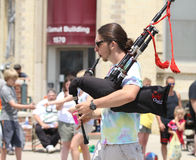 Man playing bagpipes in a parade in small town America Royalty Free Stock Image