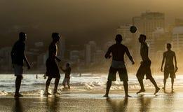 Man playing with ball at beach stock photos