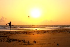 Man playing ball on shoreline at sunrise Stock Photo