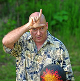 Man Playing Ball Taunting Comrades. Middle aged man making funny face and gesture to ballgame comrades stock images