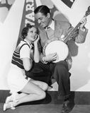 Man playing banjo for adoring woman Royalty Free Stock Photos