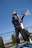 Man Playing Basketball. A young basketball player going for a jump shot Royalty Free Stock Photo