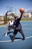 Man Playing Basketball. A young basketball player is taunting his opponent with the ball while playing one on one Stock Image