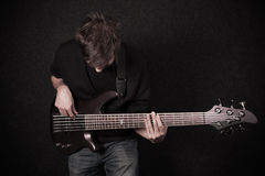 Man playing on bass guitar in studio Royalty Free Stock Photos