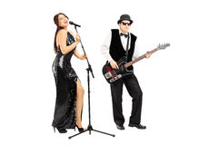 Man playing a bass guitar and woman singing Stock Images