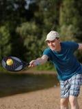 Man playing beach tennis Stock Images