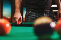 Man playing billiard. Billiard room on the background Stock Photography