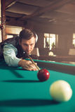 Man playing billiard. Young man concentrating while playing billiard Royalty Free Stock Photography