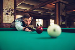 Man playing billiard. Young man concentrating while playing billiard Royalty Free Stock Image